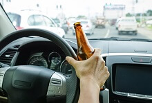 Person driving with a beer bottle in hand